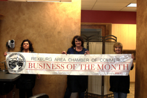B'Dazzled Hair & Nails team holding the business of the month banner.